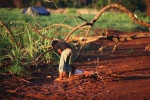 Criança ajuda uma menina alcoolizada na aldeia Apyka'i.