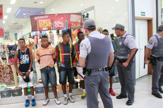 Policías abordan jóvenes en un centro comercial.