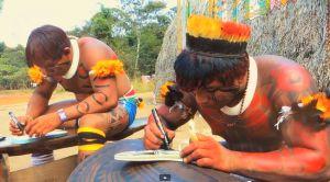 Homens fazem ilustrações indígenas nos chinelos, em Goiás.