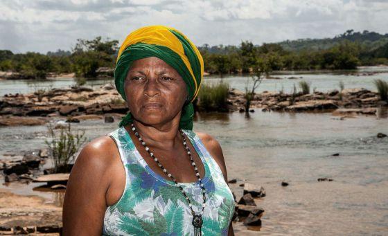 Raimunda, no rio, com uma bandeira do Brasil na cabeça porque diz que o país também é dela.