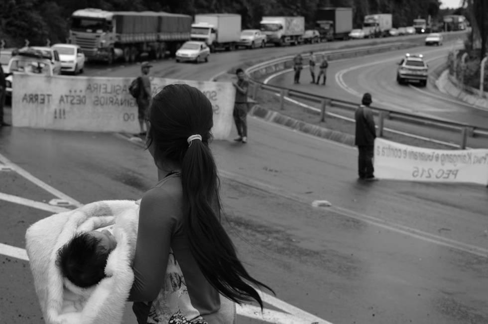 Jovem indígena com bebê no colo às margens da BR-101