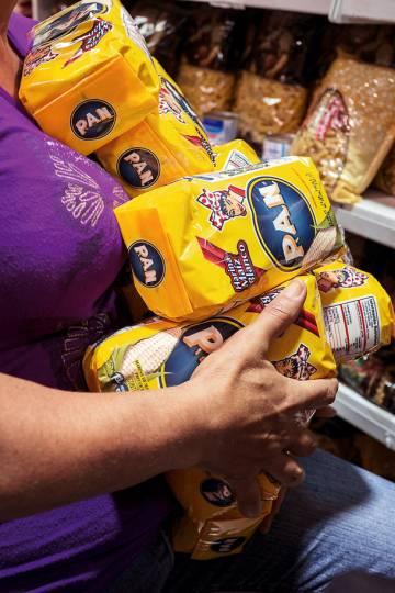Mulher carrega pacotes de farinha para arepas, um dos produtos básicos em falta.