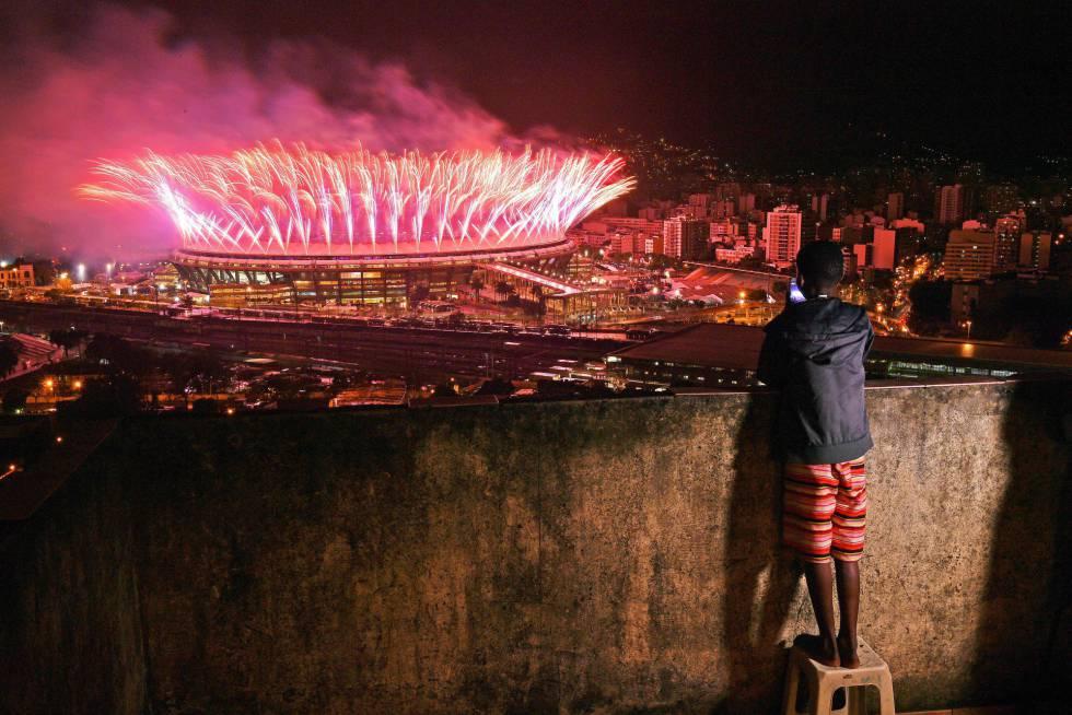 Menino assiste da comunidade da Mangueira a queima de fogos da cerimônia de encerramento da Olimpíada no Maracanã.