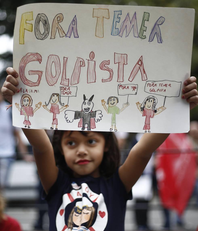 Criança segura cartaz durante ato contra Michel Temer.