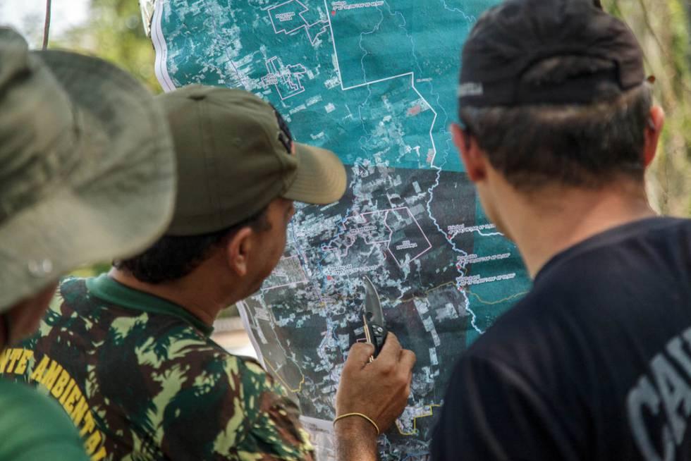 Servidores do IBAMA e indígenas observam o mapa dos arredores da Terra Indígena Mekrãgnoti.