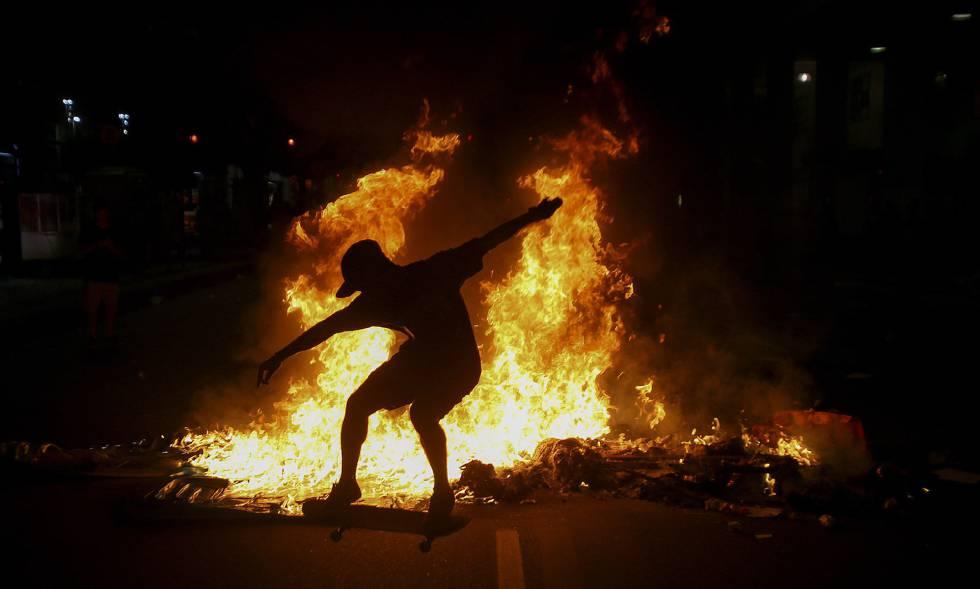 Jovem no skate em meio às chamas após a repressão policial a protesto no Rio.
