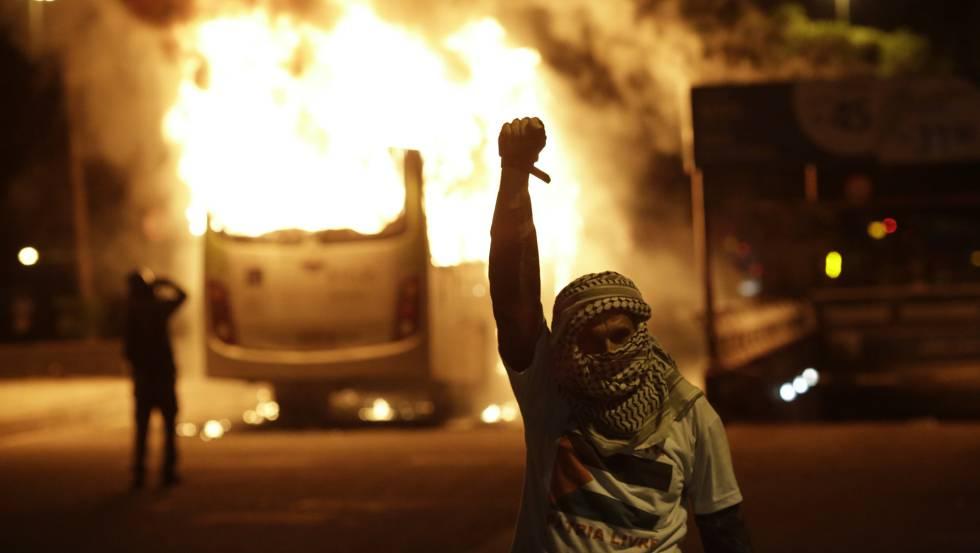 Manifestante gesticula próximo a ônibus incendiado no Rio. Polícia dispersou manifestantes com bombas de gás.