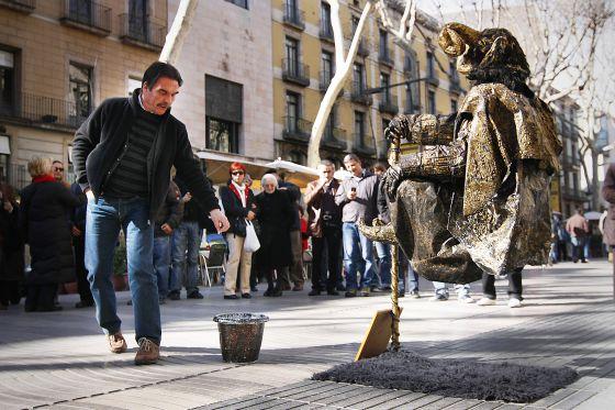 Turistas contemplando una de las estatuas más admiradas de La Rambla de Barcelona.
