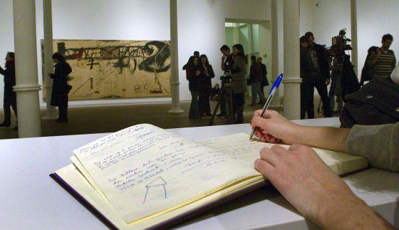 Una persona firma en el libro de condolencia situado en la fundación Tàpies de Barcelona.