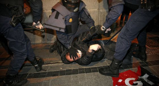 Varios policías arrestan a un manifestante.