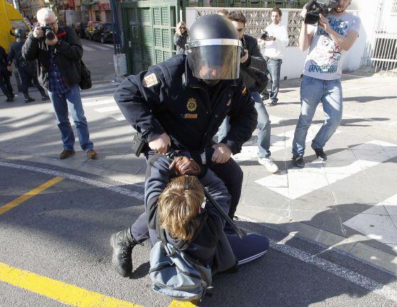 Un policía retiene a un joven estudiante contra el asfalto en el centro de Valencia.
