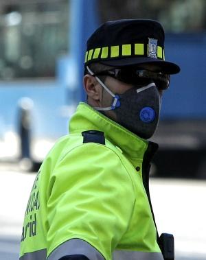 Un agente regulaba el tráfico ayer protegido con una mascarilla en el paseo de las Acacias de Madrid.