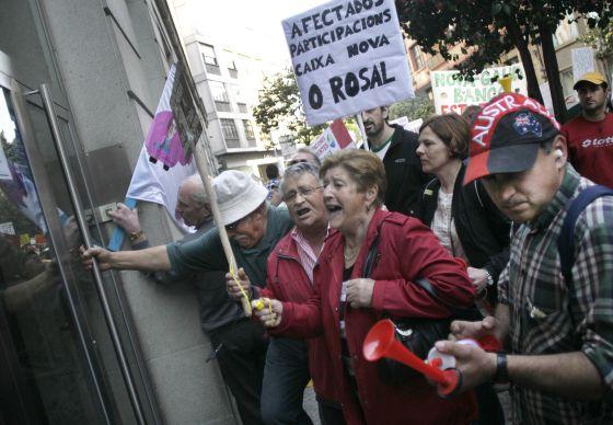 Afectados por las preferentes intentan entrar por la fuerza en una oficina de Novagalicia Banco.