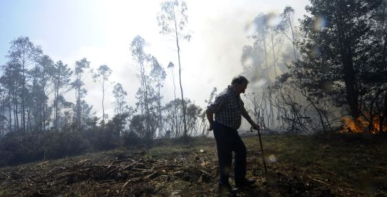 Un hombre camina cerca de las llamas en su finca en A Capela.