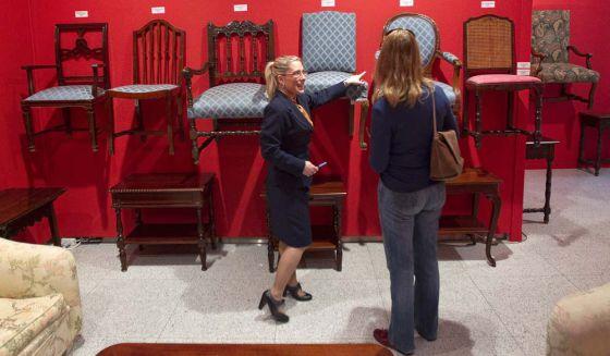 Una azafata muestra algunos de los muebles de la subasta.