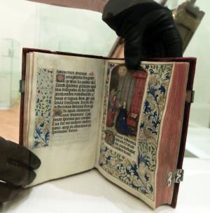 Libro de horas para los rezos, con broches metálicos y contenidos miniados.
