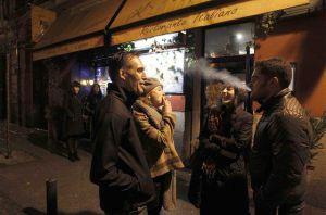 Fumadores charlando en la puerta de un bar.