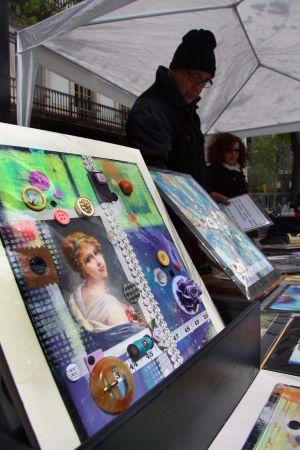 Alejandro vende sus pinturas acrílicas realizadas con objetos de costura en un puesto de la Rambla.