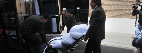 Empleados de la funeraria trasladan el cuerpo de la mujer.