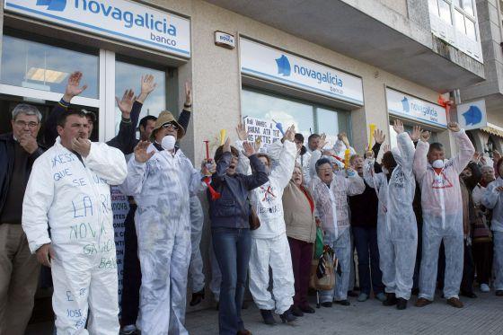 Un grupo de manifestantes protesta ayer ante una sucursal de Novagalicia Banco en la Illa de Arousa