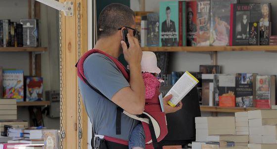 Un joven con un niño, ayer, en una de las casetas de la Fira del Llibre de Valencia.