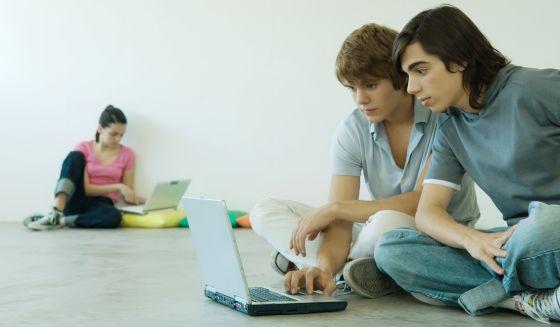 Tres adolescentes navegan por internet en una sala WiFi