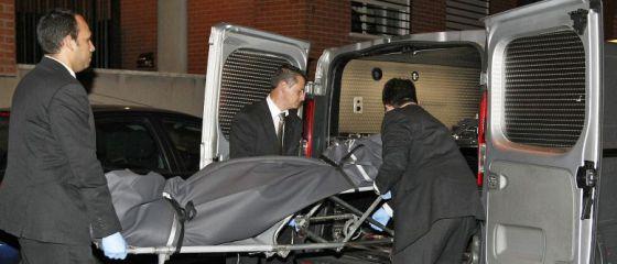 Operarios del servicio funerario retira el cuerpo de la mujer asesinada.
