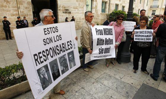 Clientes de la CAM, ante las puertas de las Cortes Valencianas.