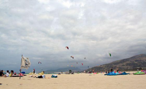Gente practicando Kitesurf en una playa de Tarifa.