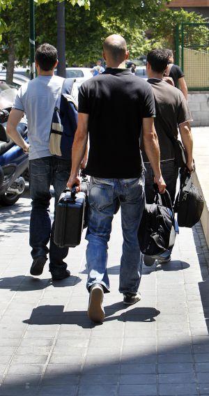 Tres agentes salen cargados de la Agencia de Turismo.