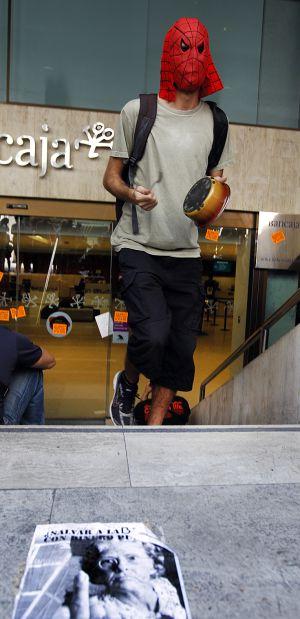 Un joven golpea una cacerola en el acceso a la sede central de Bancaja.