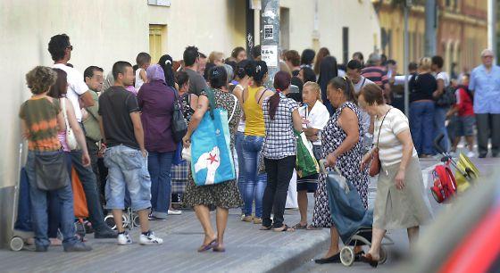 Cola de ciudadanos ante el Banco de los Pobres de Valencia para recibir alimentos básicos.
