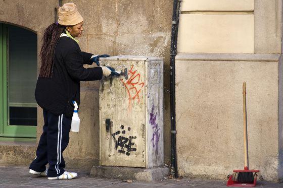 Una trabajadora limpia la calle contratada por Barcelona Activa dentro de uno de los programas sociales