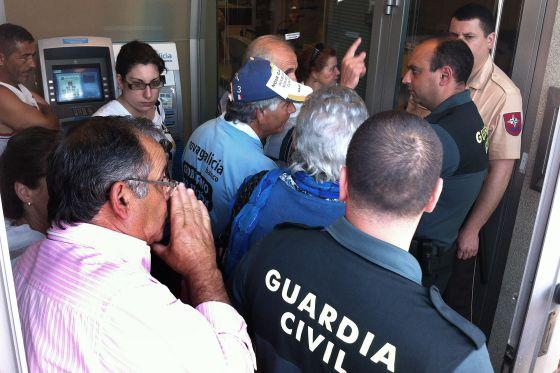 Afectados por las preferentes durante una protesta ayer en una sucursal de A Illa de Arousa.