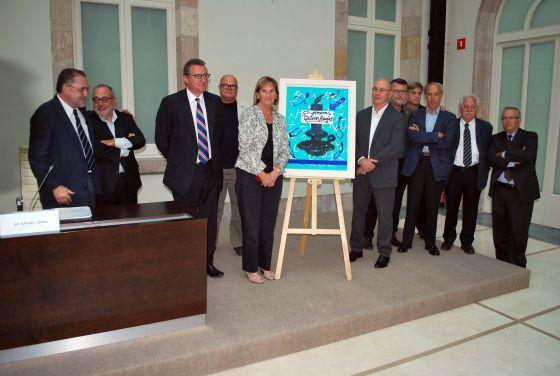 El fotógrafo Jordi Cotrina junto a la presidenta del Parlament, Nuria de Gispert, junto al premio, un cuadro de Pere Viladecans.