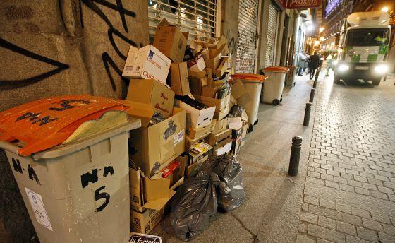 Un camión de recogida de basuras se acerca a unos contenedores llenos en una calle de Madrid