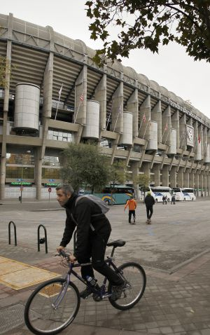 Un ciclista circula por delante del estadio Santiago Bernabéu.