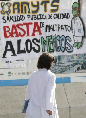 Una doctora ante una pancarta sobre la huelga.