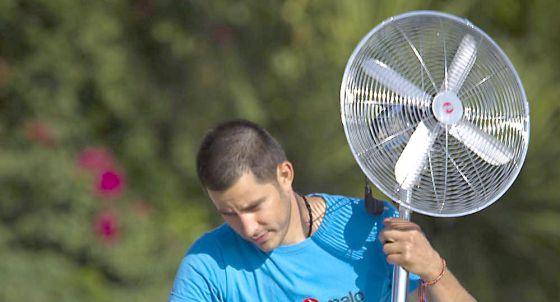 Un hombre transporta un ventilador en Sevilla.