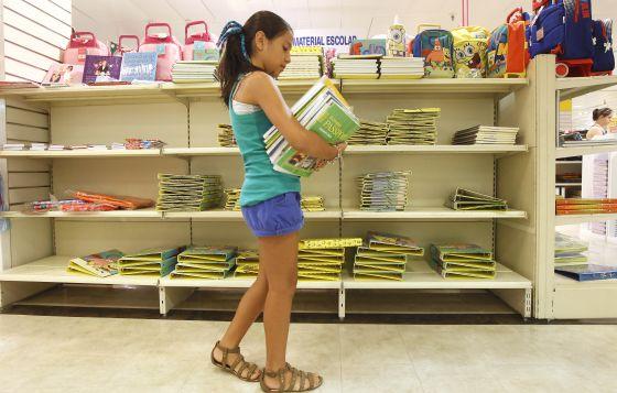 Una niña recoge libros de texto en un establecimiento comercial.