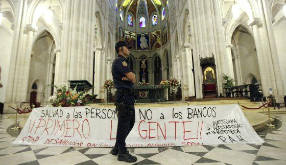 Un agente, ante la pancarta colocada por los manifestantes en el interior del templo.
