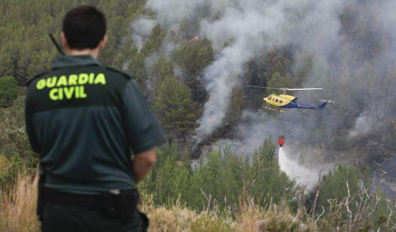 Un helicóptero descarga agua sobre el bosque en el término de Bejís.