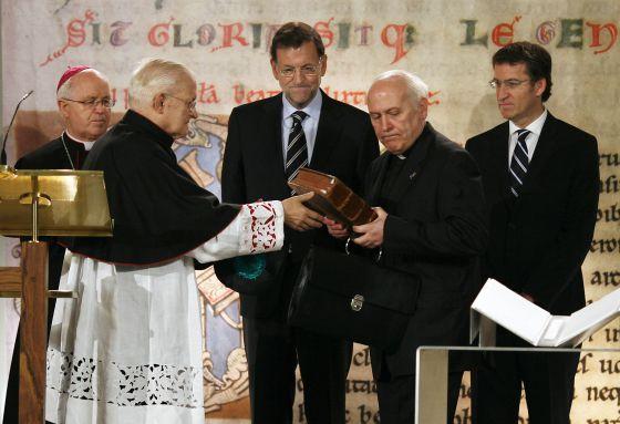 El deán de la Catedral recibe el Códice de manos del arzobispo, ante la mirada de Rajoy y Feijóo.  ANXO IGLESIAS