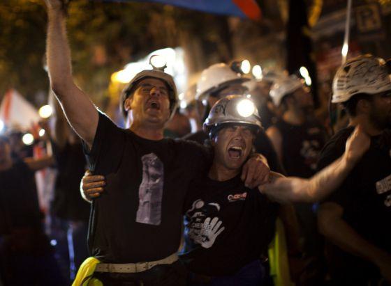 Los mineros cantan durante su recorrido nocturno por la capital.