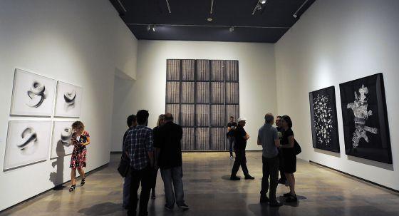 Una de las salas de la exposición 'Acontraluz', con algunos de los artistas en el centro.