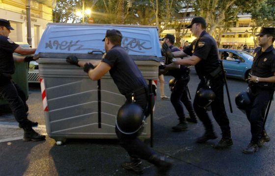 Agentes de la policía devuelven a su lugar un contenedor de basura en la confluencia de la calle Quart con la Gran Vía.