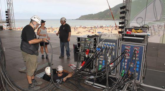 Varios operarios dan los últimos retoques al escenario de la playa de la Zurriola.