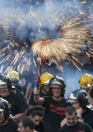 Un grupo de bomberos con fuegos artificiales, ayer en la Via Laietana de Barcelona