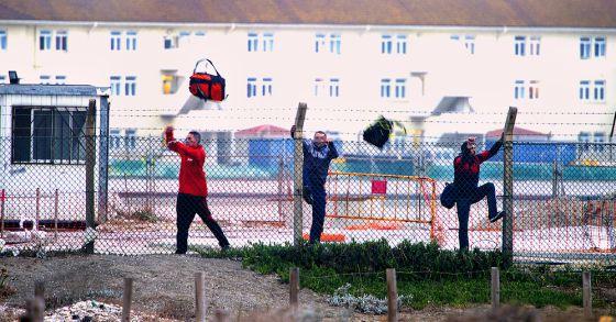 Tres hombres saltan una valla de Gibraltar con bolsas de tabaco.