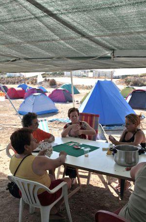 Varias mujeres juegan una partida de cartas en la acampada contra el vertedero.